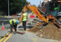 Excavating with backhoe for sewer line repair