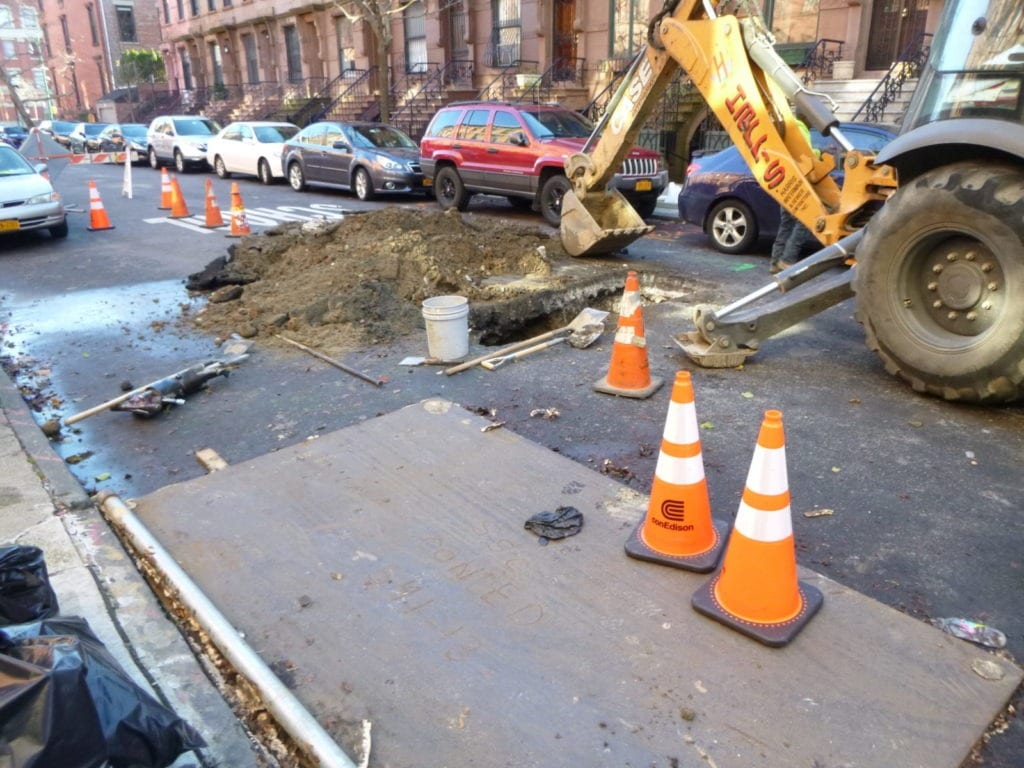 Digging in the street with a backhoe to find water main leak