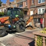 Digging with backhoe for water main installation