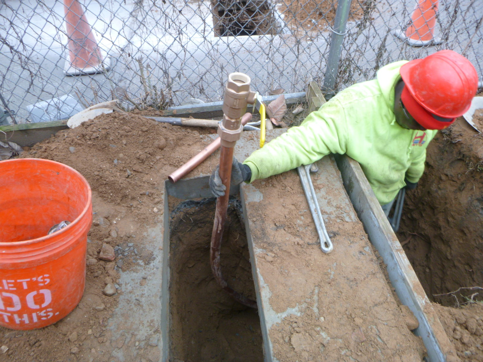 Installing main control valve for copper water main on concrete pad