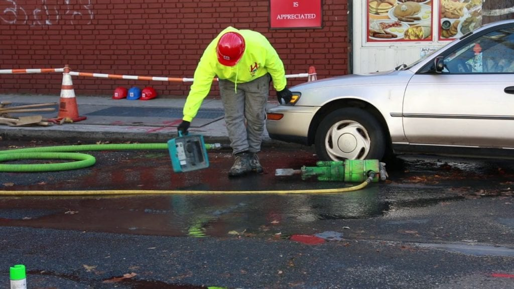 Harris Water Main and Sewer employee using a tap locator