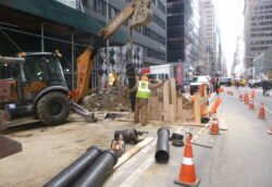 Contruction workers working on a sewer line in a city.